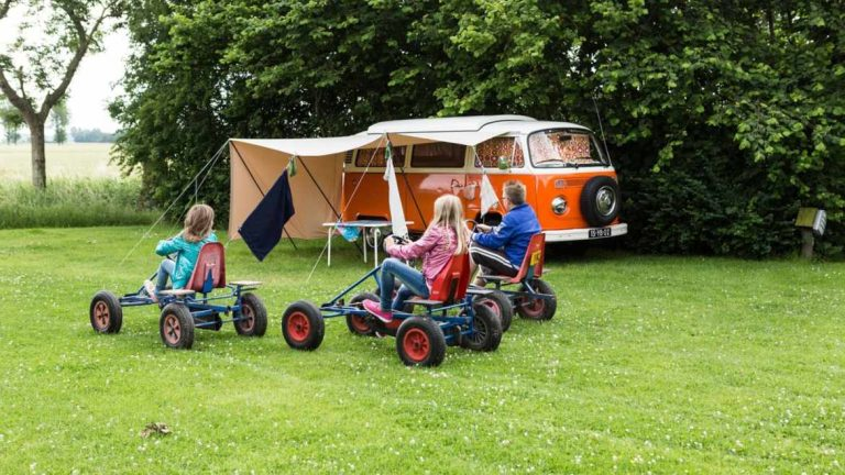 Children play camping games next to parents camping van