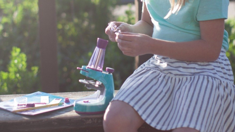 A kids microscope sits on a bench with a young girl.