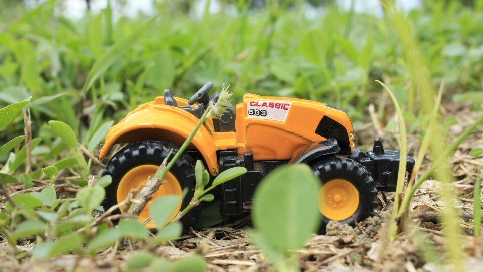 A yellow Remote Control Tractor in grass.