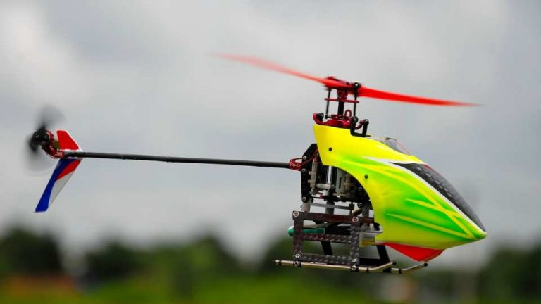 A yellow RC Helicopter in flight