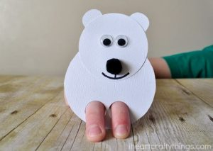 Paper polar bear with fingers poking through for legs