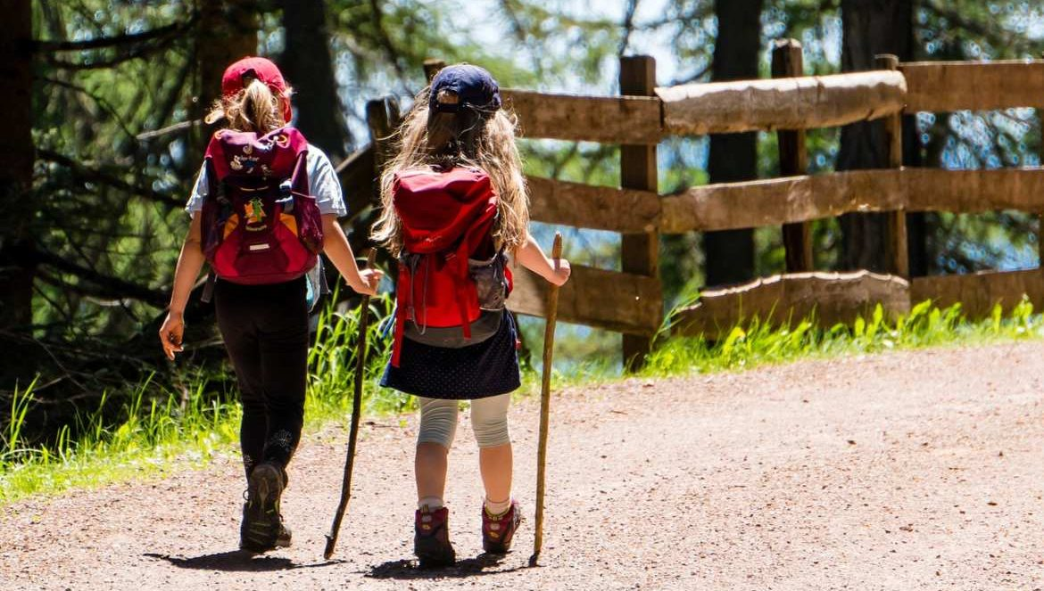 Two young girls hiking on path in woods.